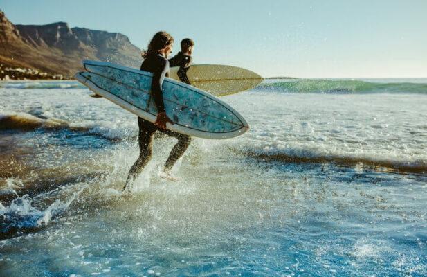 2 personas entrando a la playa hacer surf